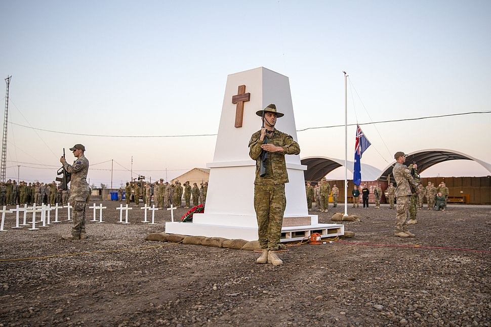 Australian and NZ soldiers present arms during an Anzac Day dawn ceremony at Camp Taji in April 2018
