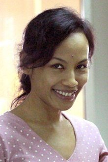 An Indonesian woman, looking forward and smiling. She is wearing a purple v-neck shirt