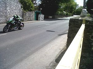 Ballagarey Corner, Isle of Man -  Rider at speed passing Ballagarey House in 2013 with the actual Ballagarey Corner, a right-kink in the direction taken by competitors, in the background