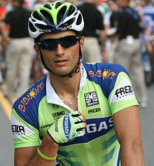 A cyclist wearing a green and blue jersey with white trim, a matching helmet and glove on his right hand (the only one visible), and sunglasses. His right hand hovers around the zipper on the front of his jersey, and vaguely visible behind him are three people in black shirts and khaki pants.