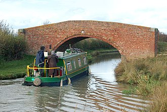 Barby, Northamptonshire - A narrowboat approaches a bridge over the Oxford Canal west of Barby