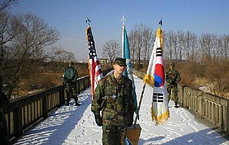 Bridge of No Return - U.S. Army Soldier posing during a ceremony at the middle of the bridge, in front of the flags of UN, the US and South Korea, while two guards are facing toward North Korea.