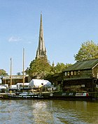 A tall church spire over a quayside with wooden sheds and boats covered with tarpaulins. In front of these on the water a twin masted sailing boat and a narrowboat
