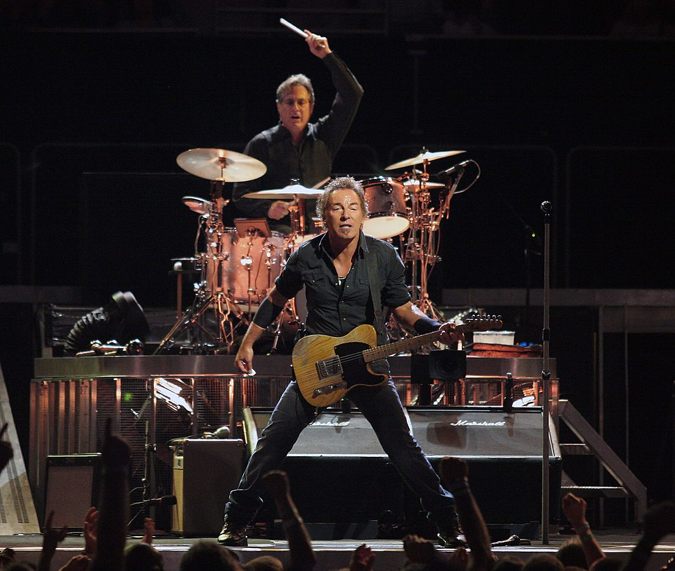 A man in dark clothing standing on a stage while holding a guitar in front of a crowd. Behind him is a man with his arm raised, holding a drum stick and sitting behind a drum set.