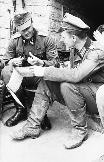 An Oberleutnant from the army sitting with a SS-Hauptsturmfuhrer from the Waffen-SS in 1944 Bundesarchiv Bild 101I-712-0475-03, Litauisch-lettische Grenze, Lagebesprechung.jpg