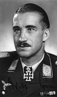 The head and shoulders of a young man, shown in semi-profile. He wears a military uniform with various military above his left breast pocket and an Iron Cross displayed at the front of his shirt collar. On his upper lip is a moustache, his hair is dark and short and combed back, his facial expression is a determined and confident smile; his eyes gaze into the distance.