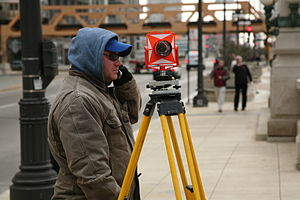 Surveying - A surveyor at work with a retroreflector used for distance measurement and orientation.