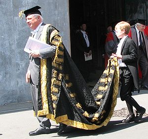 Page (servant) - Lord Patten, robed as Chancellor of Oxford University, assisted by a page