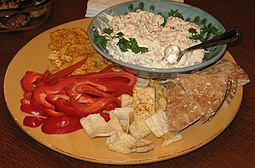 Chunky clam dip with various foods for dipping