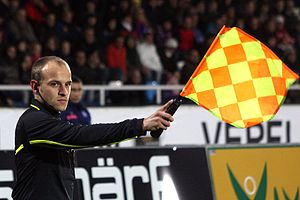 Offside (association football) - An assistant referee signals for offside by raising his flag