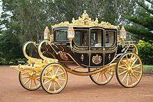 A very ornate coach, black with gold trim, a coat of arms on the door