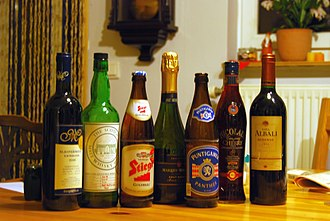 Alcoholic drink - A selection of alcoholic drinks. From left to right: red wine, malt whisky, lager, sparkling wine, lager, cherry liqueur and red wine.