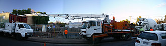 Concrete pump - Because it is a fluid, concrete can be pumped to where it is needed. Here, a concrete transport truck is feeding concrete to a concrete pumper, which is pumping it to where a slab is being poured.