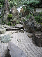 Rock garden with raked gravel and large stones including one placed like a bridge.