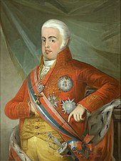 Three-quarter length portrait of a man with white hair, facing left, wearing a red coat and yellow breeches and waistcoat, a prominent sash with sword and various medals and ribbons. His right hand is tucked into the waistcoat, his left elbow rests on a pillar.