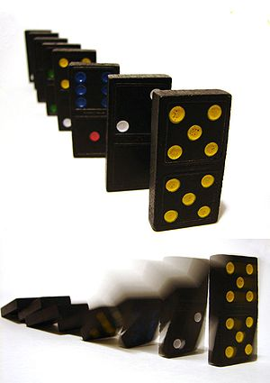 Domino effect - (Top) Dominoes are standing. (Bottom) Dominoes are in motion.