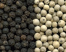 Black peppercorns on the left and white peppercorns on the right