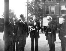 Black-and-white photograph of six men standing: All of them are well-dressed in suits and ties. Cope has short hair, mustache, and a small beard; in his hands he holds a wide-brimmed hat and some papers.