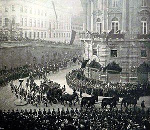 Photo en noir et blanc montrant un cercueil tiré par quatre paires de chevaux empruntant une rue courbe et entouré par des forces de l'ordre qui contiennent une foule assez dense.