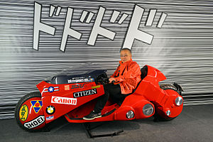 Akira (manga) - Otomo posing on a replica of the futuristic motorcycle driven by Kaneda in Akira (2016)