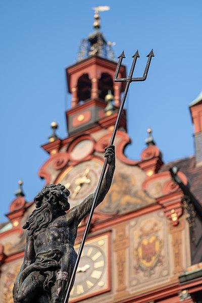 Figur auf dem Neptunbrunnen in Tübingen mit Rathaus im Hintergrund 001.jpg
