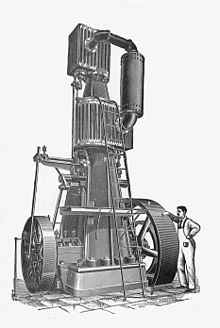 A tall vertical steam engine with one small cylinder above a second larger cylinder. The engine is around 20 feet high and dwarfs the figure of a mechanic standing alongside.