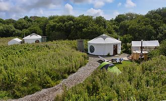 """Glamping - A glamping """"village"""" with semi-permanent yurts, gravel paths and a hot tub"""