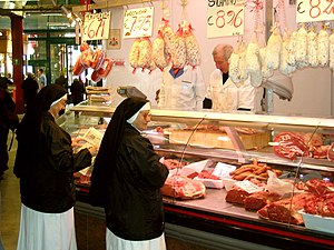 two nuns buy meat by a butcher in Florence.