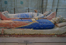 Two above ground tombs with reclining statues on top. The near tomb has a male crowned figure holding a sceptre, with his robes painted blue and red. The far tomb has a female crowned figure holding an open book with her robes painted blue.