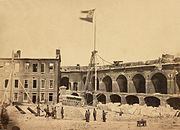 1861 photograph of the interior of a damaged military fortification. The flag of the Confederate States of America flies from a flagpole near the center of the photograph.