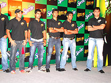A group of men standing, wearing black t-shirts and blue faded jeans. All of them are looking to the left of the image. The backdrop has alternate black and green boxes.