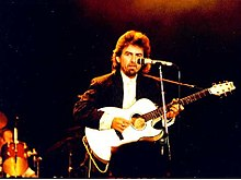 Harrison in his forties, wearing a white shirt and a black jacket, 1987