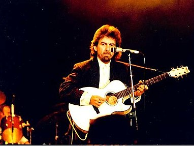 Harrison in his forties, wearing a white shirt and a black jacket, playing a white acoustic guitar and standing behind a microphone. A drummer is partly visible behind him.