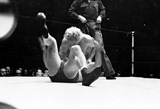 Gorgeous George - George attempting to pin another wrestler during a match, 1949