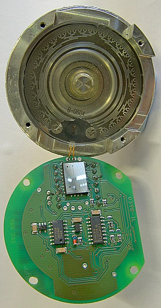 Rotary encoder - A Gray code absolute rotary encoder with 13 tracks. At the top,  the housing, interrupter disk, and light source can be seen; at the bottom the sensing element and support components.
