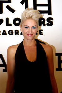 A light-skinned blonde-haired woman is dressed in a black sleeveless shirt.