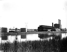 A factory on a river bend, viewed from across the river