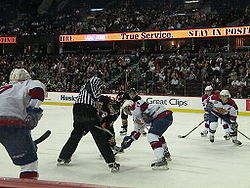 An official wearing black and white stripes conducts a faceoff as several players from two teams anticipate the start of play.