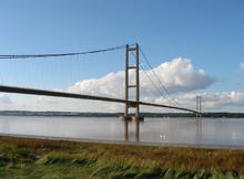 La jetée proche d'un pont suspendu enjambant les eaux bleues calmes d'un large estuaire de la rivière.