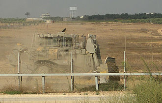 Israel–Gaza barrier - IDF Caterpillar D9R armored bulldozer working in the Palestinian side of the Israel-Gaza barrier in order to expose explosive devices
