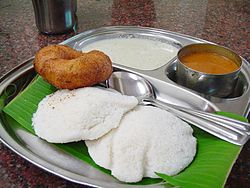 The South Indian staple breakfast item of Idly, Sambhar and Vada served on a banana leaf.