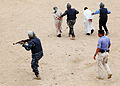 Iraqi police students escort simulated criminals away from a building while practicing clearing a building at the police academy in Basra, Iraq, April 20, 2011 110420-A-YD132-152.jpg