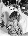 Irmgard zit met een pop op de arm naast een versierde kerstboom, Bestanddeelnr 189-1120.jpg