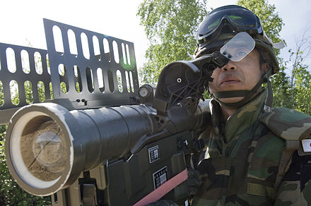 A JASDF soldier uses the optical sight on the Type 91 Kai MANPAD to acquire a mock airborne target. The prominent vertical metal devices on the left are the IFF antennas. JASDF Type91 SAM, in Alaska(USAF photo 080613-F-4127S-012).jpg