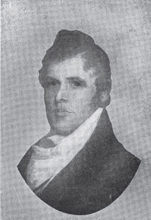 A man with thick, black hair wearing a white shirt and dark jacket