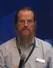 A color photograph of a man in glasses with thinning reddish-brown hair and a full beard, holding a microphone and wearing a name badge.
