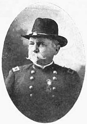 Head and shoulders of a white man with a Van Dyke beard and mustache wearing a military uniform with a cavalry hat.