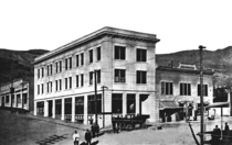 A black and white photograph of the recently opened Cook Bank building in 1908 from the diagonally opposite corner of the intersection. The bank is a three-story white masonry building with many windows on the two visible sides and a door on each side. A cornice wraps around the building at the roofline; the roof is flat. About twelve people are in the street outside the building, along with a car, and three telephone utility poles. A two-story building with awnings is directly attached to the longer side of the bank building (to the right). The road slopes upward to the left, passing a single story building. Hills are visible in the background.