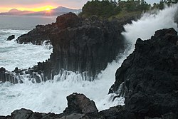 Jungmun Daepo Columnar Joints with waves crashing.jpg