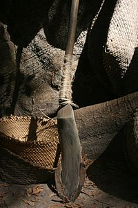 A metal blade attached to the base of a wooden rod resting against a tree trunk and various wicker products